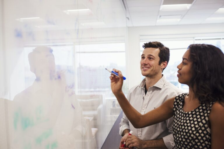 A man and a woman standing in a classroom in front of a whiteboard.
